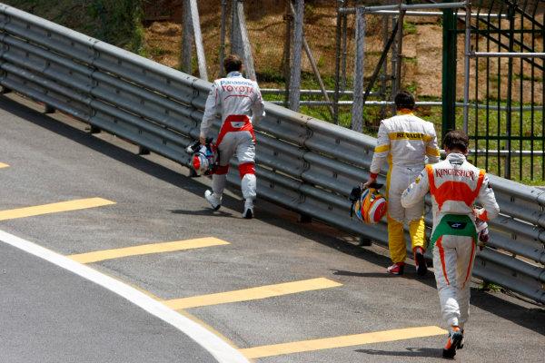 Alonso (giữa) thất thiểu đi bộ về gara sau khi bị tai nạn ở GP Brasil 2009